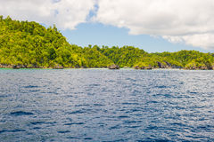 Rocky coastline of island spotted by islets and covered by dense lush green jungle in the colorful sea of the remote Togean Island Stock Image