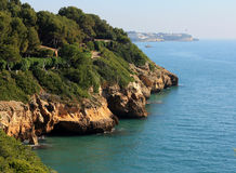 Rocky coastline and jungle near the sea with blue sky. Costa dourada. Spain Stock Photos