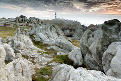 Rocky coastline and lighthouse Stock Images