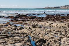 Rocky coastline with lighthouse in distance Royalty Free Stock Photography