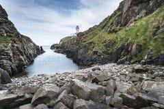 Rocky coastline and lighthouse, Northen Ireland royalty free stock image
