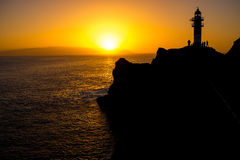 Rocky coastline with lighthouse on the sunset Stock Photo