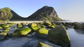 Rocky coastline on Lofoten Islands, Norway. Green stones on the Utakleiv beach on Vestvag Island, Lofoten Archipelago, North Norway, Scandinavia stock video