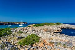 Rocky coastline of Mallorca with beautiful turquoise water and yachts in a bay. Spain Royalty Free Stock Images