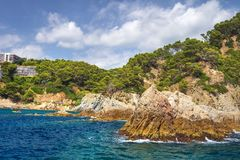 Rocky coastline of mediterranean sea in Lloret de Mar, Costa Brava, Spain on sunny summer day. Rocks, blue sea and green pine forest on mountain. Beautiful stock image