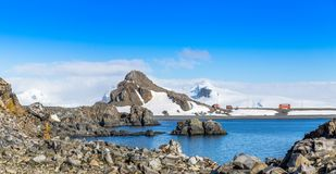 Rocky coastline panorama with snow mountains and polar research. Station buildings, Half Moon island, Antarctic peninsula
