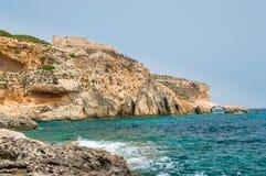 Rocky coastline with Saint Saint Mary's Battery in Comino Island in Malta. Stock Image