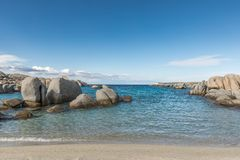 Rocky coastline and sandy beach at Cavallo island near Corsica. Deserted sandy beach and boulders on coast of Cavallo island near Corsica in France with blue Stock Photo