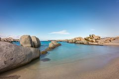 Rocky coastline and sandy beach at Cavallo island near Corsica. Deserted sandy beach and boulders on coast of Cavallo island near Corsica in France with blue Royalty Free Stock Image