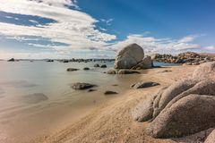 Rocky coastline and sandy beach at Cavallo island near Corsica. Deserted sandy beach and boulders on coast of Cavallo island near Corsica in France with blue Stock Photography