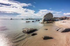 Rocky coastline and sandy beach at Cavallo island near Corsica. Deserted sandy beach and boulders on coast of Cavallo island near Corsica in France with Stock Image