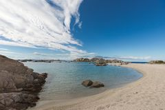 Rocky coastline and sandy beach of Cavallo island near Corsica. Rugged and rocky coastline  and deserted sandy beach of Cavallo island near Corsica in France Stock Photography