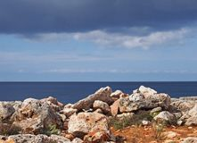 Rocky coastline scene with white stones against a calm blue sea and sky with sunlight and clouds. A rocky coastline scene with white stones against a calm blue stock photography