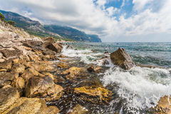 Rocky coastline, sea background Stock Images