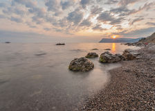 Rocky coastline, sea background, sunset Stock Photography