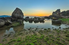 Rocky Coastline Sunrise Vietnam. A rocky coastline sunrise with moss covered rocks looking out over the south China sea in Vung Lam Bay Vietnam Stock Photo