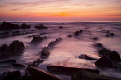 Rocky coastline sunset. Scenic view of waves on rocky ocean coastline with slow motion blue and sunset background Stock Photo
