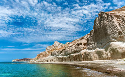 Rocky coastline of Thira. Views of the rocky coastline of the Greek island of Thira or Santorini and blue sky with spindrift clouds Stock Photos