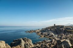 Rocky coastline and Genoese tower at Punta Spano in Corsica. Rocky coastline and transparent turquoise Mediterranean sea below the Genoese tower at Punta Spano stock images