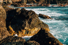 Rocky coastline and turquoise colored ocean waves Royalty Free Stock Photography