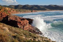 The rocky and colorful coast near Carrapateira with Amado beach in the background and strong waves, Costa Vicentina, Algarve. Portugal royalty free stock image