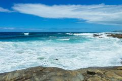Ocean Waves Summer Rocky Cove Coastline. Rocky cove beach summer blue ocean waves crashing water power along scenic coastline landscape Royalty Free Stock Photography
