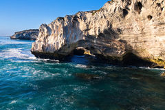 Rocky cove and ocean wave crashing into an eroded arch. Rocky cove with ocean wave crashing into an eroded arch stock photo
