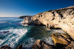 Rocky cove and ocean wave crashing into an eroded arch. Rocky cove with ocean wave crashing into an eroded arch royalty free stock image