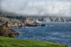 Rocky Creek Bridge, Big Sur. A classic photo of the Rocky Creek Bridge near Big Sur, California with a marine layer hanging low Royalty Free Stock Images