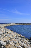 Rocky curved dam near black sea Royalty Free Stock Photo