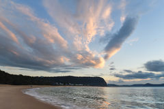 Rocky Dawn Seascape. Cloud fingers at Pearl Beach, Central Coast, NSW, Australia Royalty Free Stock Photo