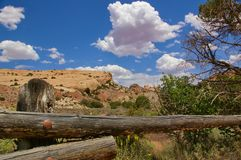 Rocky desert landscape with wooden fence in the foreground, blue sky with white clouds, Canyonlands National Park, USA. Rocky desert landscape with wooden fence Royalty Free Stock Image