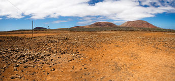 Rocky and dry plain. With mountains in the background Stock Photos