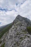 Rocky edge of mountain, mount Catria, Apennines, Marche, Italy. Rocky edge of mountain, blue sky with clouds, Corno of mount Catria, Apennines, Marche, Italy Stock Photo