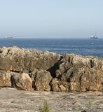 Rocky embankment at a cave A mouth of a devil Portugal (Boca do Inferno) with the ships in background Royalty Free Stock Photo