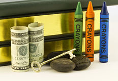 Rocky Financial Times for Schools. Gold key is placed on rocks that are next to money and crayons with books behind.  Although education is the key to the future Stock Photography