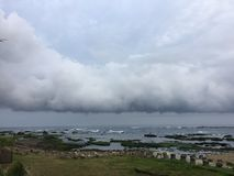 Rocky foreshore and low cloud over the sea Stock Photo
