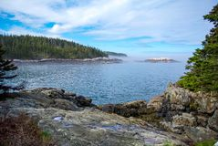 Rocky Forested Coast in Maine. The rocky coast of a bay on the Isle au Haut in Maine.  Part of Acadia National Park.  Rocky shore with forested interior and see Stock Photos