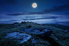 Rocky formation on grassy hillside at night. Rocky formation on grassy hillside. beautiful scenery of Runa mountain in summertime at night in full moon light stock images