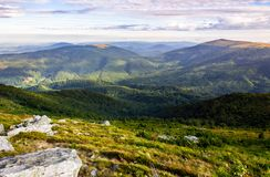 Rocky formations on the grassy hills. Beautiful mountainous scenery in late summer. colorful grassy carpet on the hillside. forested mountains in the distance royalty free stock image