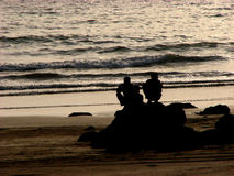 Rocky Friends. Two friends sitting on the beach on a rock at sunset in India Stock Images
