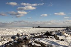 Rocky frozen Lake Superior shoreline with lighthouses and shipping pier in Duluth, Minnesota, USA in winter. Frozen Lake Superior shoreline with lighthouses and royalty free stock images