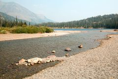 Rocky and gravelly shoreline of Upper Two Medicines Lake in Glacier National Park during the 2017 fall forest fires in Montana USA royalty free stock images