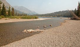 Rocky and gravelly shoreline of Upper Two Medicines Lake in Glacier National Park during the 2017 fall forest fires in Montana USA royalty free stock photos