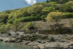 Rocky green hills along Hozugawa River. Hozugawa River along the rocky green hills with train tracks. Arashiyama, Kyoto. Japan Royalty Free Stock Photos