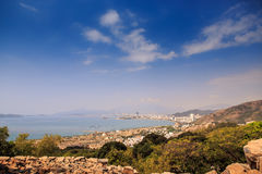 Rocky Green Hills contro le nuvole luminose del cielo del mare blu Fotografia Stock