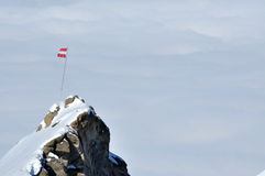 Rocky height in the Alps with the flag of Austria Stock Photography