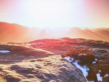 Rocky hill above inverse mist. Winter cold weather in mountains. Colorful fog. Misty valley in winter mountains royalty free stock photos