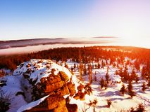 Rocky hill above inverse mist. Winter cold weather. In mountains, colorful fog. Misty valley in winter mountains. Peaks of mountains above creamy mist stock photos