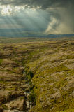 Rocky hill with heavy storm and creek Royalty Free Stock Image